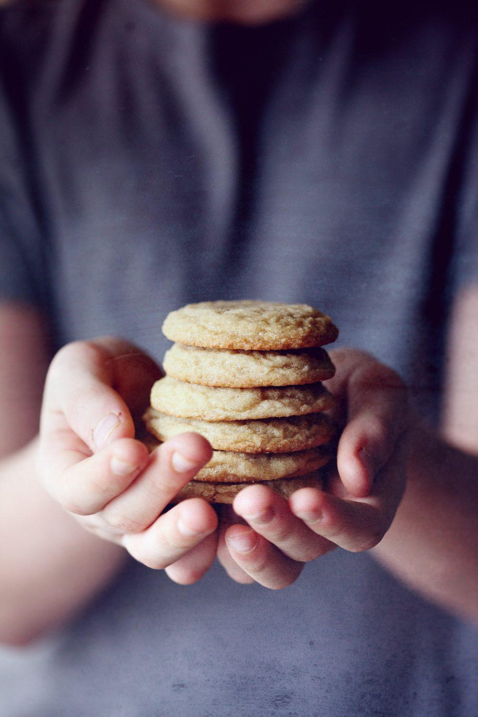 En person håller fram staplade kakor med båda händerna